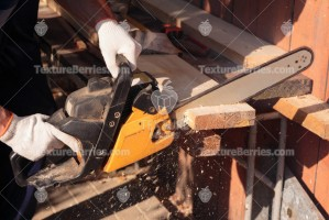 A carpenter cuts lumber with chainsaw, sawdust fly to side