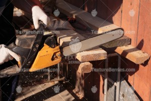 A carpenter cuts wood plank with chainsaw, sawdust fly to side