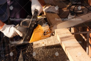 A man cuts lumber with chainsaw, sawdust fly to side