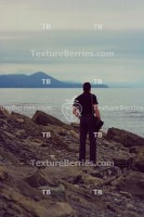 Back view portrait of man standing on a seashore, feeling of loneliness and sadness