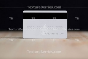 Backside of white credit card with embossing on wooden table over black wall