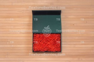 Black box with red filler on bamboo, top view