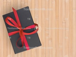Black gift box with red bow on wooden background
