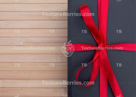 Black gift box with red bow on wooden table