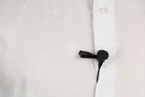 Black lavalier microphone on white man's shirt