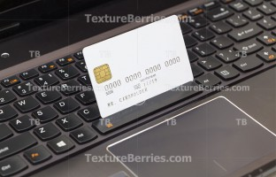 Blank credit card on laptop keyboard, online shopping concept