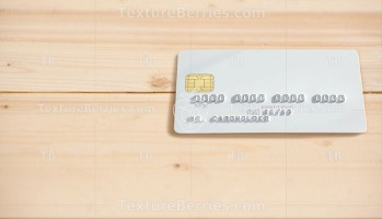Blank white bank card on wooden table background