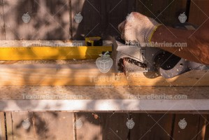 Close-up of a carpenter with power tool while planing a piece of wood