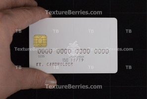 Hand holding white blank credit card on black background