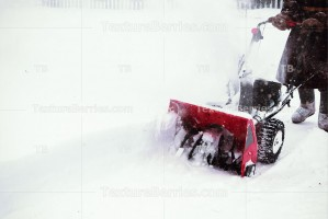 Man clears snow with snow blower after winter snowfall