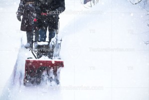 Man clears snow with snow blower, winter snowfall