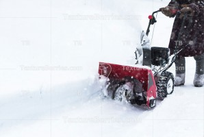 Man clears snow with snowblower after winter snowfall