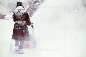 Man in sheepskin coat clears snow with snow blower
