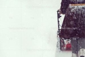 Man in sheepskin coat clears snow with snowblower