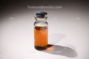 Medical glass vial with brown liquid on gray background