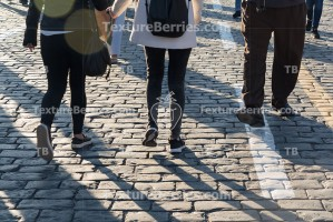 Pedestrians on cobblestone pavement, people traffic, shadows