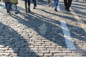 Pedestrians on cobblestone pavement, people traffic with shadows