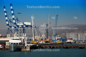 Ship staying in the port with harbor cranes background
