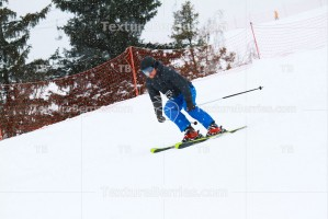 Skier skiing downhill on ski resort during snowfall