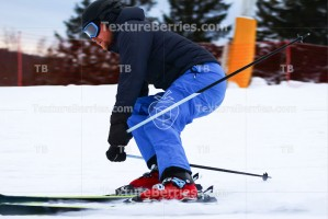 Skier skiing downhill on ski resort in evening