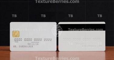 Two sides of white credit card with embossing on wooden table
