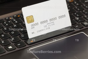 White credit card on laptop keyboard, online shopping concept