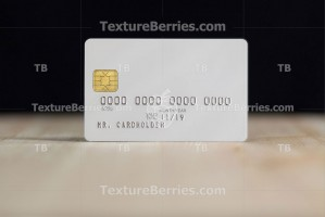 White credit card with embossing on wooden table over black wall
